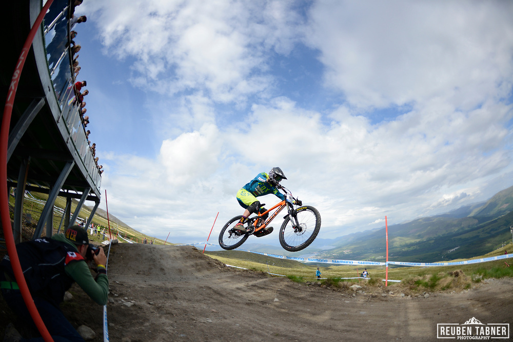 Magnus Manson grabs some air whilst crowds watch from above at the top of the Fort WIlliam downhill track during Saturday practise at the UCI Mountain Bike World Cup.