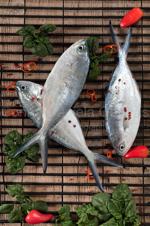 Raw trevally fish on iron grill seasoned with valerian, red pepper and peppercorns.