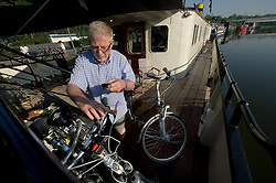 Tourists from Germany enjoy a Boat and Bike tour through Flanders. A tour member prepares his bike aboard the MS Magnifique, in Bruges, Belgium on Sunday, July 11, 2010. (Photo © Jock Fistick)