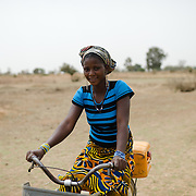 A woman carrying a jerry can of water home on a bicycle from a dam in Koala, Burkina Faso on 27 February 2014. In the absence of an accessible improved water source, community members rely on a dam which is also used by animals, and a small number of shallow, hand-dug, low-yield wells.
