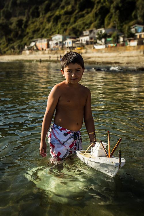 COCHOLGUE, CHILE - MARCH 19, 2014:  Joaquin Bastidas, 9, poses for a portrait with a homemade styrofoam boat, crafted to look like an artisanal fishing boat. Although his father is an artisanal fisherman, Joaquin says he doesn't want to follow in his footsteps. He said he would rather be a sailor. PHOTO: Meridith Kohut for The World Wildlife Fund