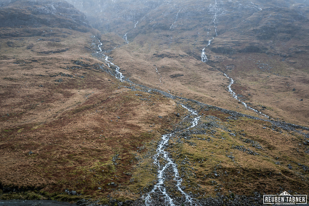 A stream in spate flows down the hill side in Glen Etiv, in the Highlands of Scotland.