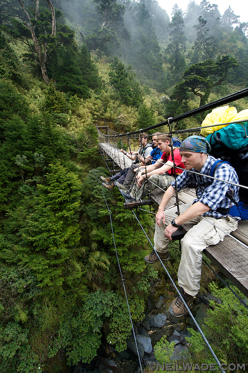 Trekkers take a break on a suspension bridge high above a small stream on the NengGao hiking trail in Taiwan.