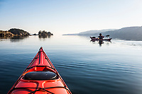 Sea Kayakers glide over the glassy water as they leave Ganges Harbor headed toward Captain Passage, Salt Spring Island, BC, Canada.