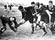 Kel Tremain toes the ball into the face of Welsh halfback and captain Clive Rowlands at Cardiff, 1963. With Tremain are, from left: Waka Nathan (partially obscured), John Graham and Colin Meads.<br /> Photosport