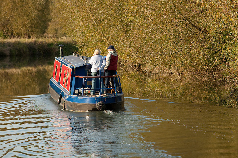Barge cruising the River Thames in autumn near Newbridge, Oxfordshire, Uk