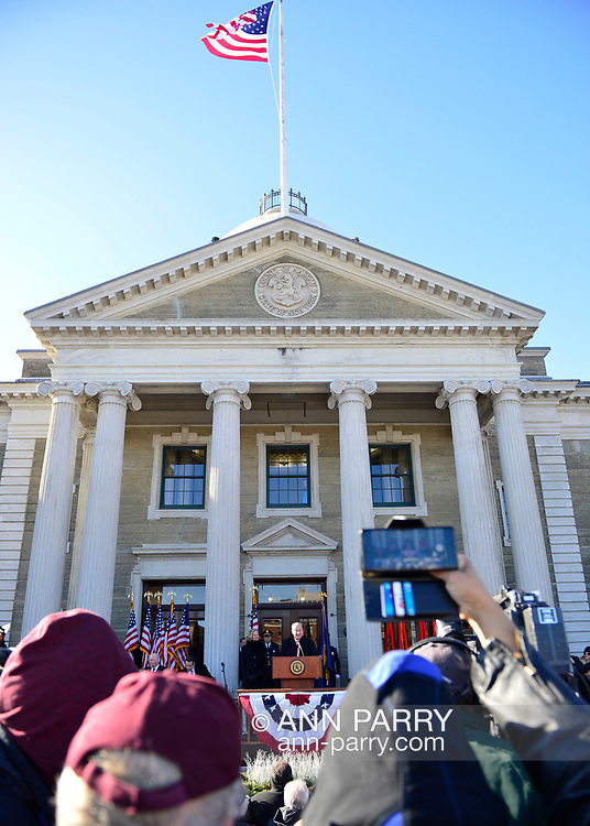 Mineola, New York, USA. January 1, 2018. Speaking at podium is U.S. Senator CHUCK SCHUMER of New York, and left of him is Nassau County Executive LAURA CURRAN, at historic swearing-In of CURRAN as County Executive, the first female County Executive. Temperature was a freezing 14 ℉ Fahrenheit / -10 ℃  Celsius for the outdoor ceremony held in front of Theodore Roosevelt Executive & Legislative Building, and people in audience, some taking cell phone photos, stood close together on and near the vast entrance stairs steps.