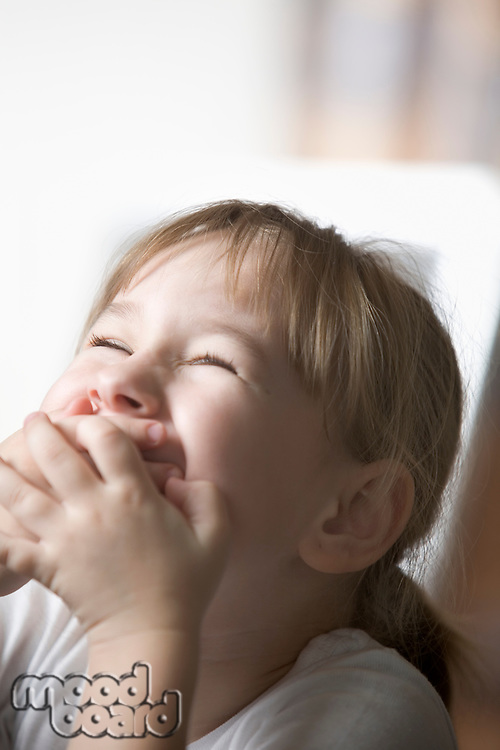 Girl laughing with hands over mouth