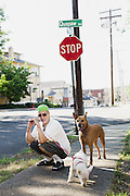 HOT SPRINGS, AR – JUNE 29, 2013: Don Jordan stops to pose with his dogs while walking in a residential neighborhood.