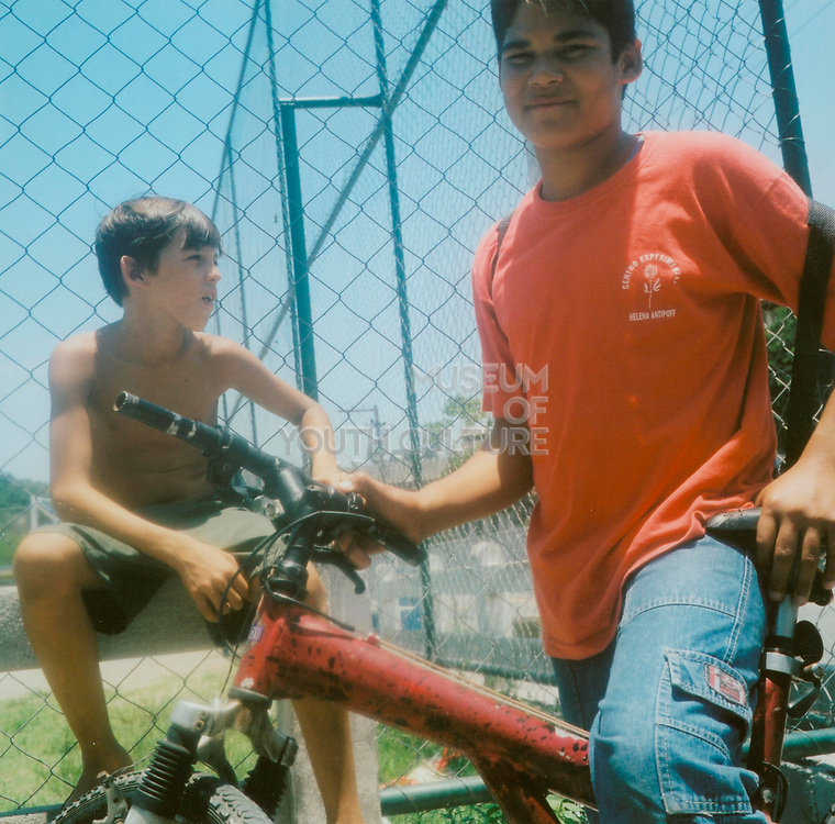 Two boys one sitting on his bike the other on a fence Brazil