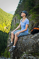 A woman hiker sitting on the edge of a rocky cliff looking up at a mountain, Little Si Trail, Washington, USA.