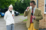 © Licensed to London News Pictures. 29/04/2014. Slough, UK. Nigel Farage drinks tea, watched by a supporter, whilst waiting to take part in a live radio interview.  NIGEL FARAGE leader of UKIP in Slough today 29 April 2014 to congratulate local activists on more than doubling the candidates the party will field in local elections. Photo credit : Stephen Simpson/LNP