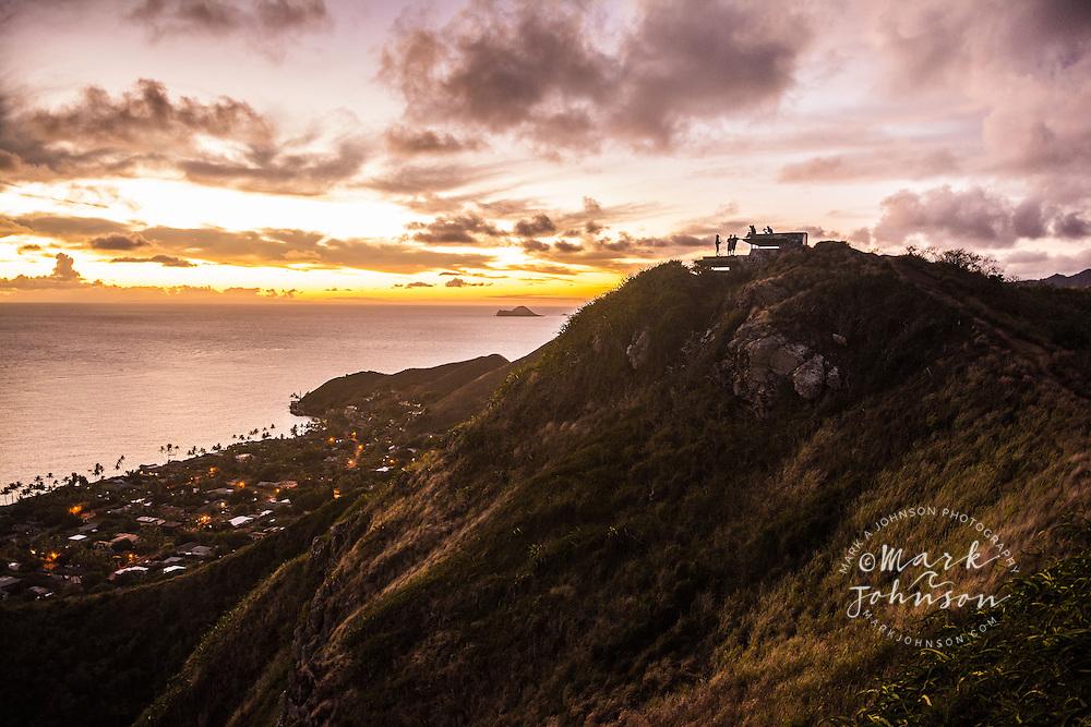 Early morning hikers enjoy the sunrise over Lanikai atop a WWII era pillbox, Kaiwa ridge trail, Kailua, Oahu, Hawaii