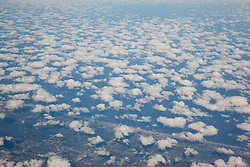 Aerial photograph of some clouds and land from an airplane window.