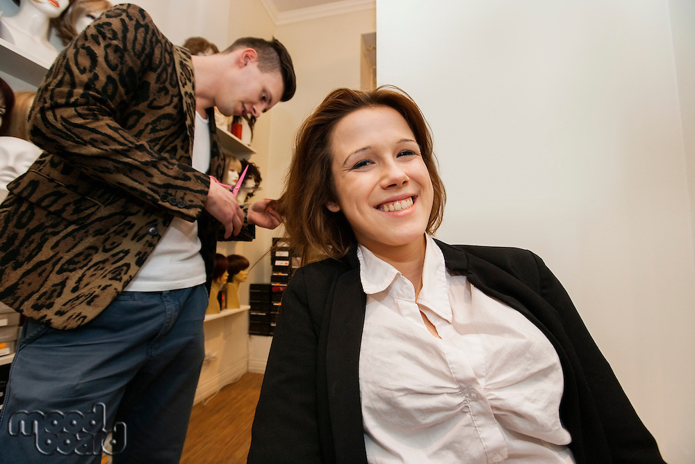 Portrait of happy female customer getting haircut in beauty salon