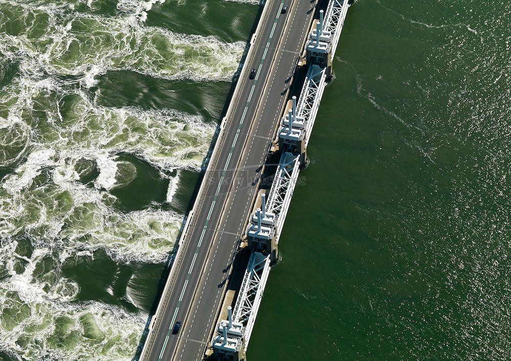 Stormvloedkering Oosterschelde tussen de Noordzee en Oosterschelde, waarbij tijdens opkomend water het water door de kering geperst wordt.