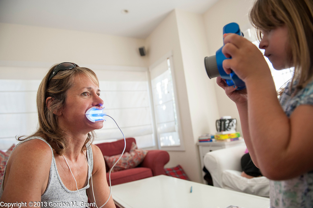 East Hampton, NY - 7/27/13 - Patient Kathryn Alisbah, with daughter Lindsay, 6,  while getting her teeth whitened by Dr. Jeffrey Rappaport and Dr. Michelle Katz at her home in East Hampton, NY July 27, 2013. CREDIT: Gordon M. Grant for The Wall Street Journal<br /> NYTEETH