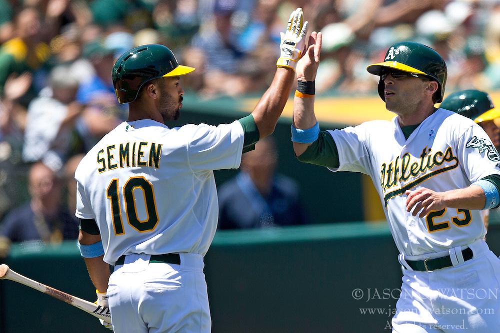 OAKLAND, CA - JUNE 21:  Sam Fuld #23 of the Oakland Athletics is congratulated by Marcus Semien #10 after scoring a run against the Los Angeles Angels of Anaheim during the third inning at O.co Coliseum on June 21, 2015 in Oakland, California. The Oakland Athletics defeated the Los Angeles Angels of Anaheim 3-2. (Photo by Jason O. Watson/Getty Images) *** Local Caption *** Sam Fuld; Marcus Semien