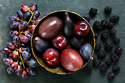 Dark Exotic Fruits on slate background including passion fruit, plums, figs, grapes, black berries