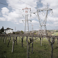 A house dominated by high voltage pylons near th poerhouse of Villanova (PE). The powerhouse is currently being upgraded to cope with the influx of electricity coming from the Balkans and the energy demand of the new power line of 380Kv. Once upgraded, the skies in this area will literally be covered by a grid of cables.<br /> Villanova (PE).
