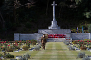 An army officer looks at the graves of military personnel who died in Japan during the war or occupation in front of the Cross of Sacrifice at Hodagya  Commonwealth War Graves cemetery on Remembrance Sunday in Hodogaya, Yokohama, Kanagawa, Japan. Sunday November 12th 2017. The Hodagaya Cemetery holds the remains of more than 1500 servicemen and women, from the Commonwealth but also from Holland and the United States, who died as prisoners of war or during the Allied occupation of Japan. Each year officials from the British and Commonwealth embassies, the British Legion and the British Chamber of Commerce honour the dead at a ceremony in this beautiful cemetery.