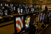 Live BBC news is being broadcast on TV screens in the John Lewis department store in Oxford Street, London, England. A newly-elected Barack Obama is seen speaking to his party faithful at a rally in Chicago, and his face is large on the many home cinema screens seen across the world's media after this historic political election which saw the election of America's first black Commander in chief. A shopper stops to watch the lunchtime news programme as Obama speaks with passion about the changes he promises to bring to America while the rest of the world looks on hoping for new political directions.