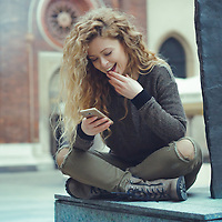young blonde woman chatting on her smartphone