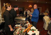 George Boyer samples appetizers from Fratello's with Rob Clifford and Hannah Rush during Altrusa's Taste of the Lakes Region on Sunday evening at Church Landing.  (Karen Bobotas/for the Laconia Daily Sun)