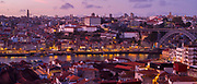 Historic river front of the Ribeira region of Porto at dusk and Dom Luis I bridge from Vila Nova de Gaia in Portugal