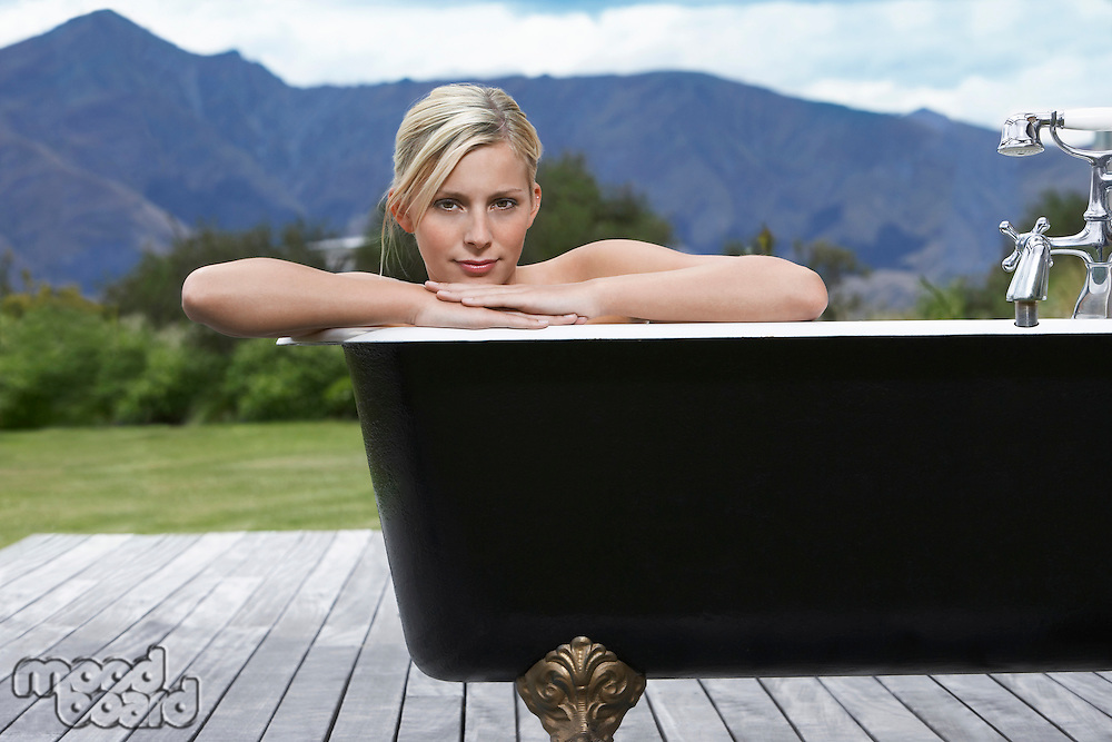 Woman in bathtub on porch by mountains