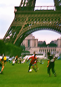 Image of the Eiffel Tower with people playing soccer on the Champ de Mars in Paris, France