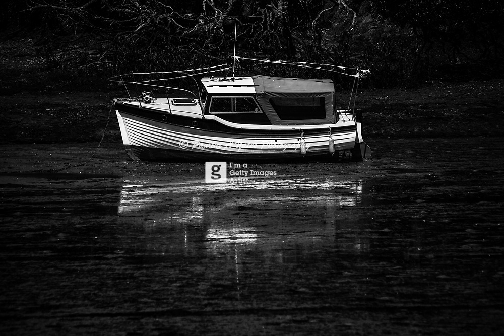 Boat stranded on the mud flats on Salcombe estuary in Devon. Reflection caught in wet mud
