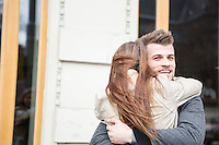 Happy young man hugging woman outside cafe