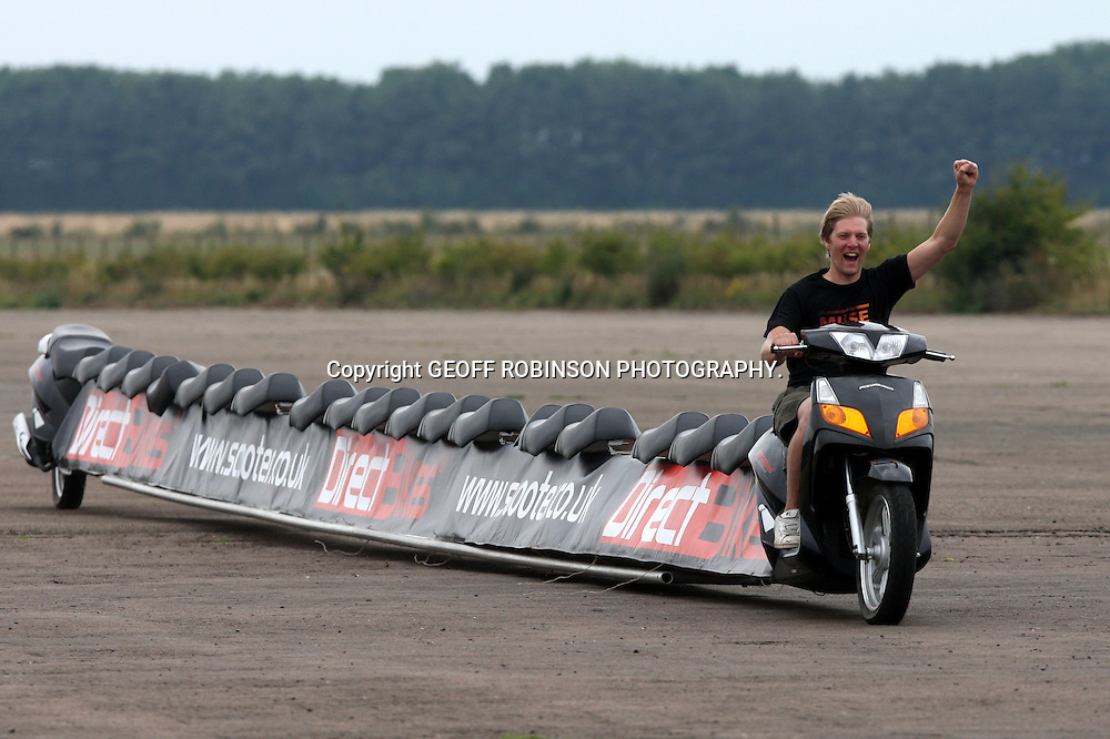 "PIC SHOWS COLIN FURZE BREAKING THE WORLD RECORD FOR  THE WORLD LONGEST MOTOR BIKE AT SALTBY AIRFIELD,LINCS... A plumber has built the world's LONGEST motorbike - which is an incredible 22 metres (72ft) long...Colin Furze, 31, spent a month building the 25-seater bike, which is as long as a TENNIS COURT...He used one-and-a-half 125cc mopeds which he extended using an aluminium frame and drove the bike a MILE along the runway at Saltby Airfield in Grantham, Lincs...He managed to get the bike, which is worth around £3,000, up to 35mph, but found it almost impossible to steer...""When I first got on it I thought it would never work and at a slow speed it's almost impossible to keep upright,"" said Colin, from Stamford, Lincs...""But once you get going it becomes a bit easier, although it is a real strain on your arms as it has such heavy steering...SEE COPY CATCHLINE World's longest motorbike"