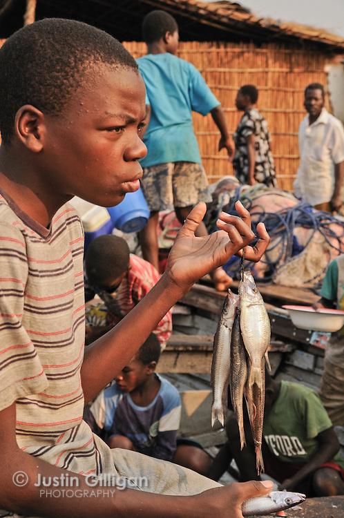 Young fisher selling catch at Senga Bay, Lake Malawi, Malawi.