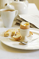 Half-Eaten Hard-Boiled Egg on dining room table With Tea