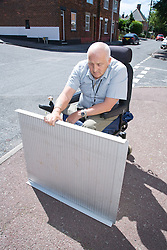 Male wheelchair user setting up a portable folding travel ramp to use at a roadside kerb,