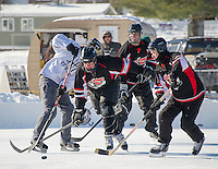 The Fifth Line and Looney Bin hit the ice on Sunday for the semi final rounds of the New England Pond Hockey Classic.  (Karen Bobotas/for the Laconia Daily Sun)
