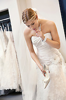 Beautiful confused woman in wedding dress holding footwear while looking down
