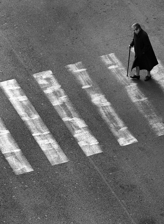 Woman walking over street in Rome Italy.