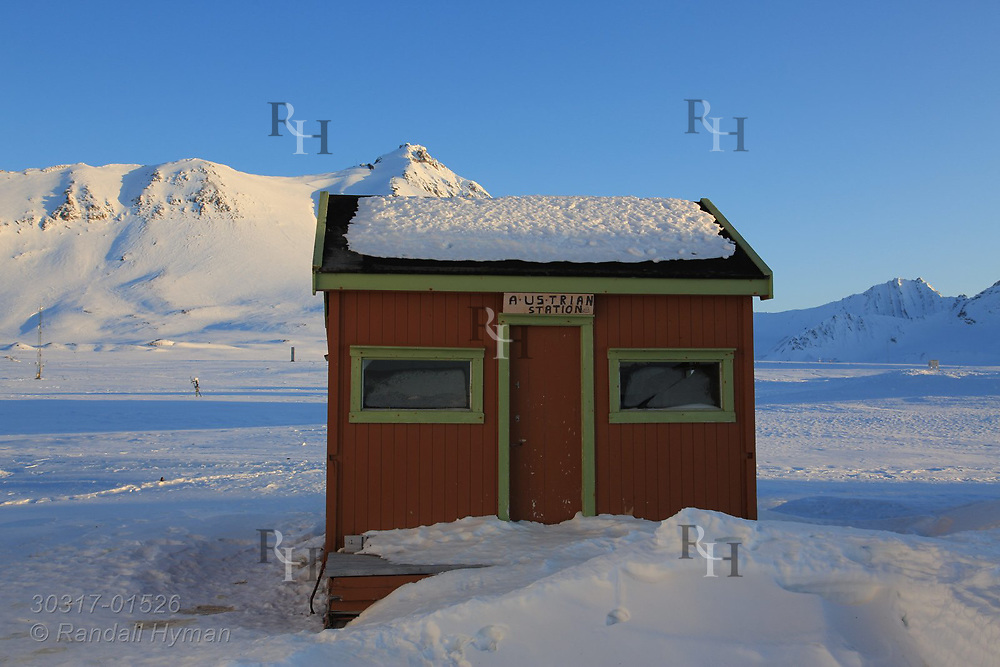 """Mock """"Austrian Station"""" sign hangs over door of a small shed at the international science village of Ny-Alesund on Spitsbergen island in Kongsfjorden; Svalbard, Norway."""