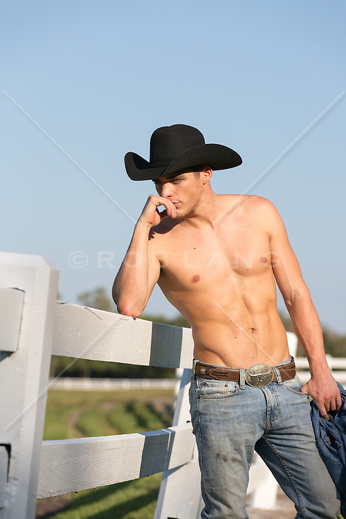 shirtless cowboy leaning on a fence