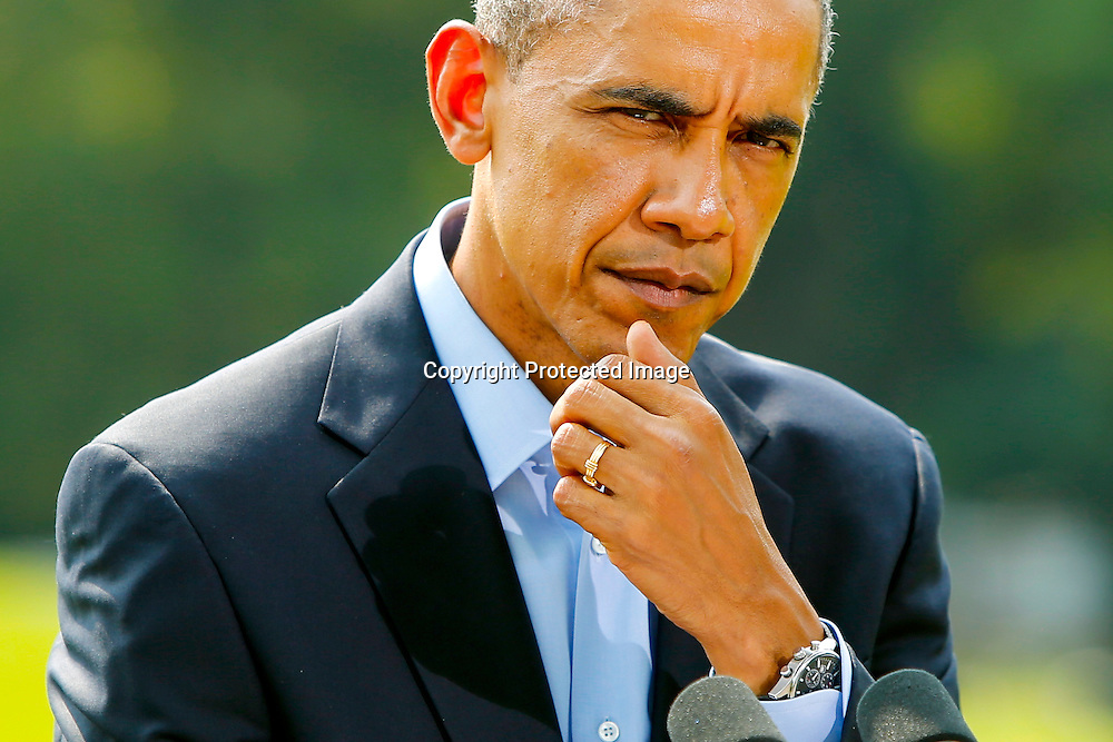 U.S. President Barack Obama listens to a question from a reporter after his statement about the situation in Iraq before departing for his vacation via Marine One helicopter from the South Lawn of the White House in Washington August 9, 2014.
