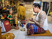 "27 MAY 2015 - BANGKOK, THAILAND:  AJARN NENG ONNUT, a revered tattoo artist in Bangkok, prays at the start of his day of tattooing people in his Bangkok home. Sak Yant (Thai for ""tattoos of mystical drawings"" sak=tattoo, yantra=mystical drawing) tattoos are popular throughout Thailand, Cambodia, Laos and Myanmar. The tattoos are believed to impart magical powers to the people who have them. People get the tattoos to address specific needs. For example, a business person would get a tattoo to make his business successful, and a soldier would get a tattoo to help him in battle. The tattoos are blessed by monks or people who have magical powers. Ajarn Neng, a revered tattoo master in Bangkok, uses stainless steel needles to tattoo, other tattoo masters use bamboo needles. The tattoos are growing in popularity with tourists, but Thai religious leaders try to discourage tattoo masters from giving tourists tattoos for ornamental reasons.    PHOTO BY JACK KURTZ"