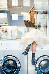 Woman in Launderette Sitting on top of Washing Machine