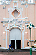 A cyclist rides past the brightly painted Caribbean style Sanctuary of Our Lady of Candlemas church in Tlacotalpan, Veracruz, Mexico. The tiny town is painted a riot of colors and features well preserved colonial Caribbean architectural style dating from the mid-16th-century.