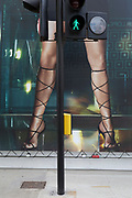 The lower limbs of a model appears on a small section of a large billboard during the renovation of a Versace outlet, at a pedestrian crossing on New Bond Street, on 26th May 2020, in London, England.