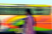 A blurred motion photo of an Indian woman wearing a purple dress next to a passing bus in front of India Gate in New Delhi, India