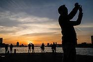 Nederland, Rotterdam, 31 okt  2015<br /> Op de Kop van Zuid kan je mooi van de zonsondergang genieten. Het is er gezellig druk als er mooie kleuren in de lucht zitten en iedereen is aan het fotograferen met smartphones.<br /> <br /> Foto: (c) Michiel Wijnbergh