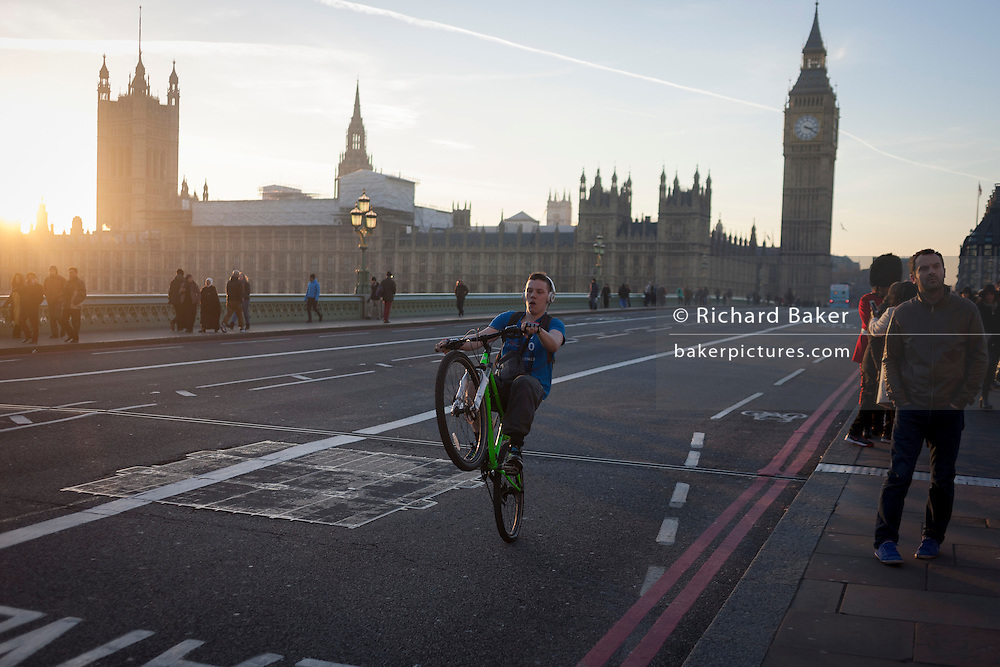 A youth balances on his rear wheel to perform a wheelie on the South side of Westminster Bridge, on 30th November 2016, in London England.